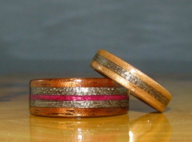 Hawaiian Koa ring with Grey Maple and Purple Heartwood bands and a Eucalyptus ring with a Grey Maple inlay