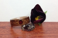 This unique Rosewood ring features a Juniper Heartwood Braid with a red Garnet centre piece.
