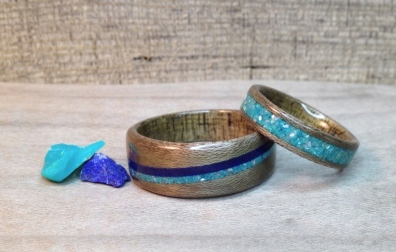These greyed maple wedding bands have Blue Pine liners. The Pine trees in the interior of British Columbia were devastated several years back from an infestation of Pine Beetles. Many trees died and needed to be cut down. You can see the lines in the wood that were left behind from the Beetles. The rock bands in these rings are Lapis & Chrysocolla.