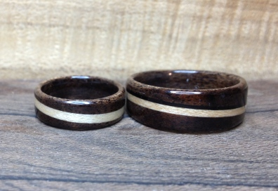 Dark Walnut wedding rings with spiralled bands of Maple. His ring has a small African Blackwood spiralled band.