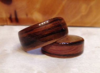 His ring is a wide Rosewood ring and her ring iis also Rosewood but has a Juniper Heartwood band and a Maple wood liner.