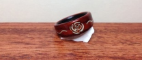 A cocobolo ring with carved rose design filled with Howlite